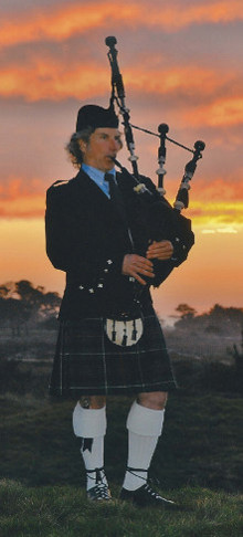 Bagpiper Michel d'Avenas in full highland dress in the sunset