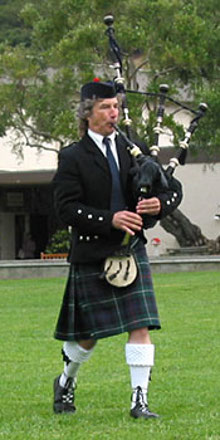 Image of bagpiper wearing a kilt and marching while playing bagpipes